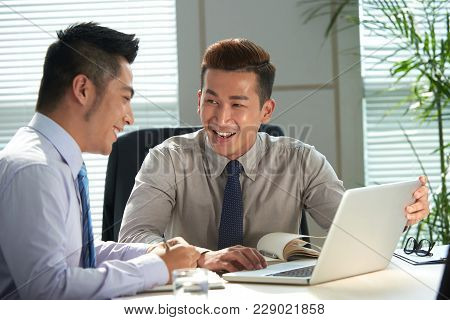 Cheerful Vietnamese Business Executives Dicussing Plans At Meeting
