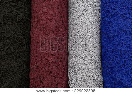 Colorful Swatches Of Lace Fabric On Shopfront. A Lot Of Fabric Rolls. Bolts Of Lace Fabric Blue, Gra
