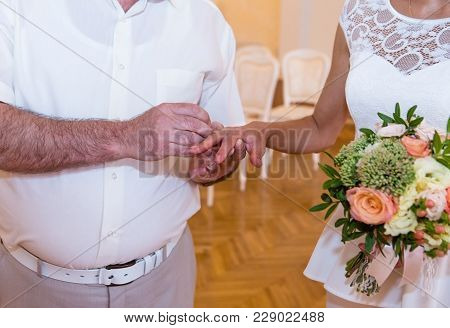 Bride and groom exchange rings in wedding day. Unequal marriage between young girl and old man. Wedding ceremony indoor. Groom puts ring on brides finger. Marriage engagement. poster