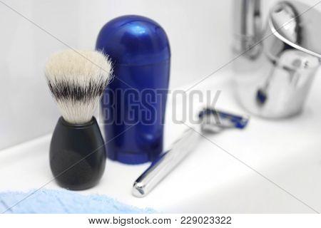 Shaving brush, deodorant and razor for man on sink