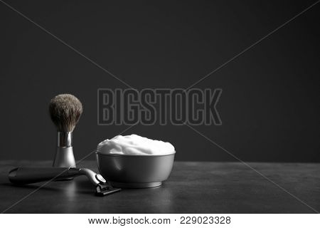Barber brush, shaving foam and razor for man on table against dark background