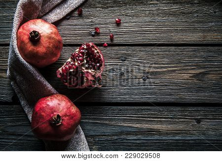 Ripe Pomegranates, Napkin And Table Knife On White Wooden Background