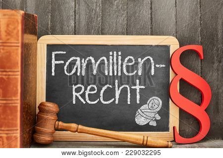 Specialist lawyer for German word Familienrecht (family law) as concept with law symbols next to blackboard