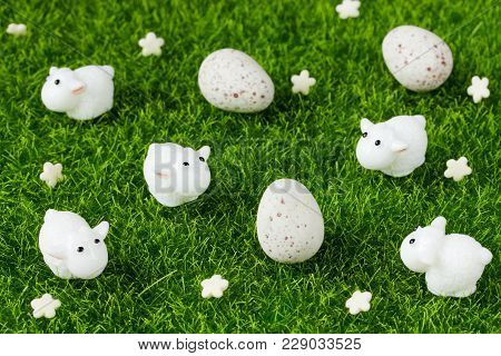 Easter Symbolic Decorations White Flowers, Mini Cute Lambs And Candy Eggs On Green Grass Background