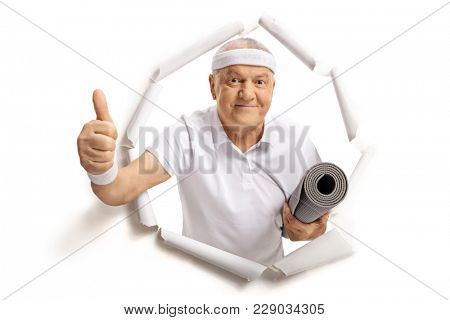 Elderly sportsman with an exercise mat breaking through paper and making a thumb up sign