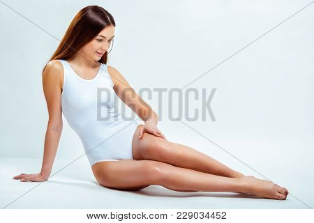 Portrait Of A Beautiful Young Woman With Long Slender Legs. Depilation