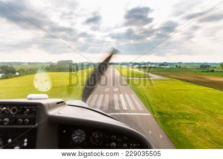 Sport pilot landing on airfield strip with propeller aircraft