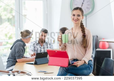 Portrait of a confident young woman holding a tablet and a coffee mug, while sitting on the desk of a co-working space for creative freelancers and entrepreneurs