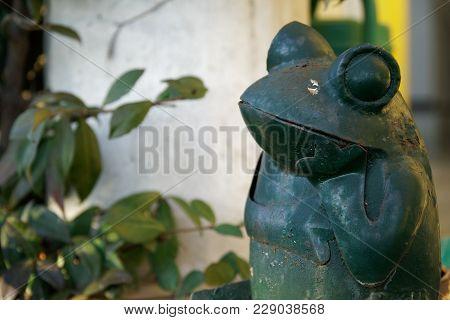 Steel Green Frog Sits In Crossed Legs Gesture On Stone Stairs. Garden Statue Selective Focus On The