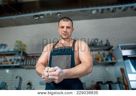 Bodybuilder Chef In Hotel Or Restaurant Kitchen Interior Knead The Dough On The Table. Pizza Cooking