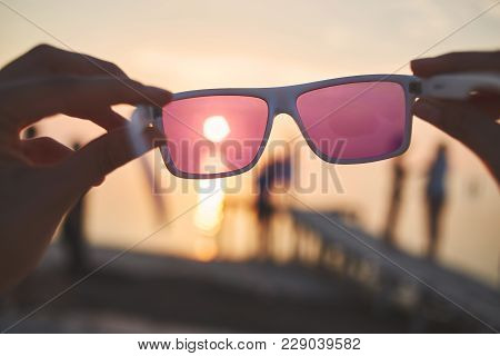 View Of The Sun, Sea And Sky Through Pink Sunglasses At Sunset. A Look At The World Through Rose-col