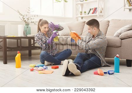 Young Couple Spring-cleaning And Having Fun. Happy Family With Spray Detergents And Various Househol