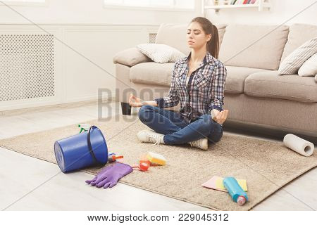 Woman Meditating, Sitting On Carpet While Cleaning Home In The Living-room, Copy Space. Housekeeping
