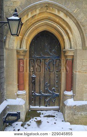 Bracknell, England - March 01, 2018: Fresh Fallen Snow Around A Wooden Door With Ornate Metal Hinges
