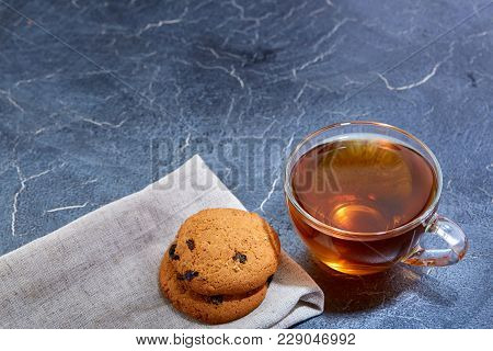A Transparent Glass Cup Of Delicious Black Tea Or Earl Grey With Cookies On Cotton Napkin Over A Dar