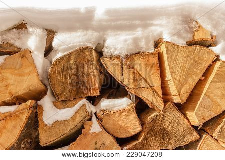 Pile Of Stacked Chopped Firewood Covered With Snow On Sunny Day, Close Up