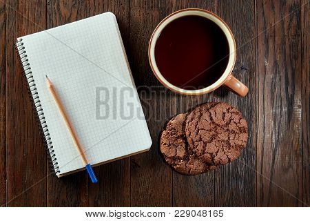 Porcelain Cup Of Black Tea Or Earl Grey With Chocolate Cookies, Blank Workbook And A Yellow Pencil O