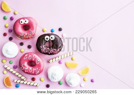 Junk food. Donuts, marmalade, chocolate sticks and balls, and meringue on a pink background. Unhealthy food concept. Top view. Copyspace poster
