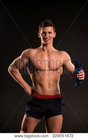 Man Athlete With Sport Bottle On Dark Background. Sportsman Smile With Fit Torso, Body. Thirst, Dehy