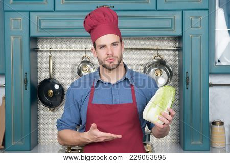 Cook Man Point Hand At Chinese Cabbage. Chef In Red Hat, Apron With Vegetable In Kitchen. Vegetarian