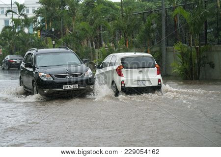 Hanoi, Vietnam - July 17, 2017: Car Splashes Through A Large Puddle On Flooded Street After Heavy Ra