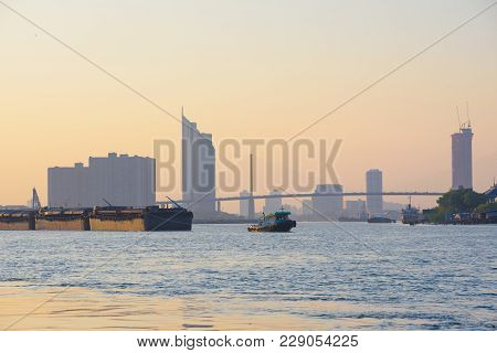 Tugboat Take Barges Downstream On The River To The Sea Under The Sunset In The City.