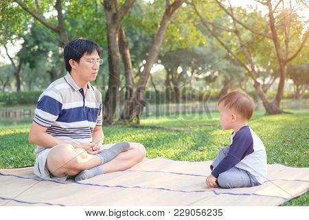 Father And Cute Little Asian 18 Months / 1 Year Old Toddler Baby Boy Child With Eyes Closed Practice