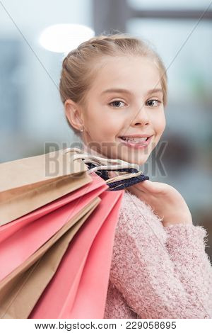 Happy Kid Looking At Camera And Holding Paper Bags In Hand