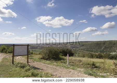 Landscape With Signboard. Signboard Is Near Road And There Is Cloudy Sky.