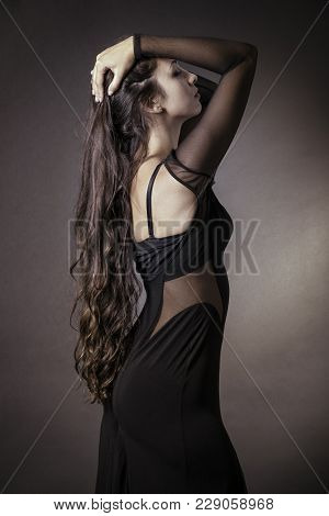 Portrait Of Young Beautiful Long-haired Latin Woman Posing Over A Black Background