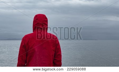 Pensive Lonely Man Standing In The Rain On The Beach And Gazing At The Dramatic Sky