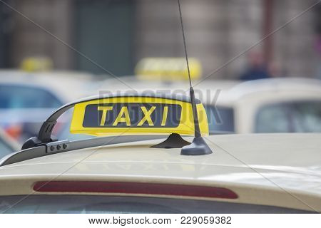 A Yellow Taxi Sign On A Taxi In The City