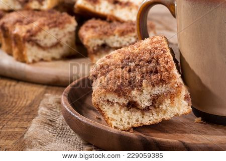 Closeup Of A Piece Of Cinnamon Swirl Crumb Cake And Coffee Cup On A Wooden Plate
