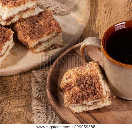 Piece Of Cinnamon Swirl Crumb Cake And Cup Of Coffee On A Wooden Plate