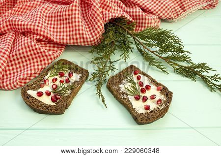 Black Bread With Grenades Berries On Turquoise Wooden Background. Christmas Food, Christmas Decorati