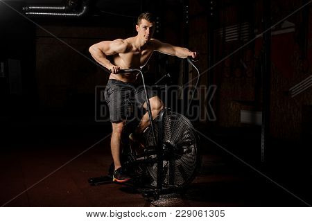 Young Sexy Shirtless Man With Brown Hair Practicing In A Dark Light Of A Gym