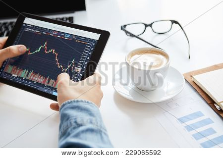 Young Trader Is Sitting In Home At Table, Working On Tablet With Graphs, Diagrams On Monitor. Crypto