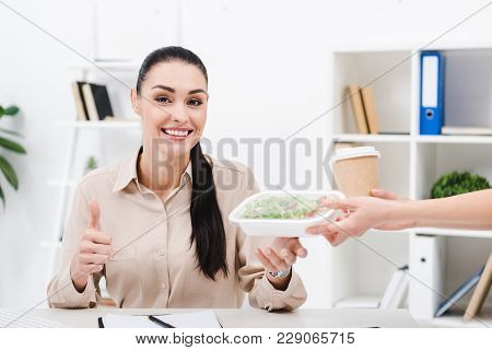 Portrait Of Smiling Businesswoman Showing Thumb Up While Taking Take Away Food From Courier In Offic