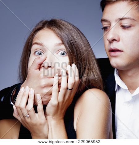 Gender Inequality And Aggression: Man Covers Woman's Mouth. (fear, Violence, Domination Concept)