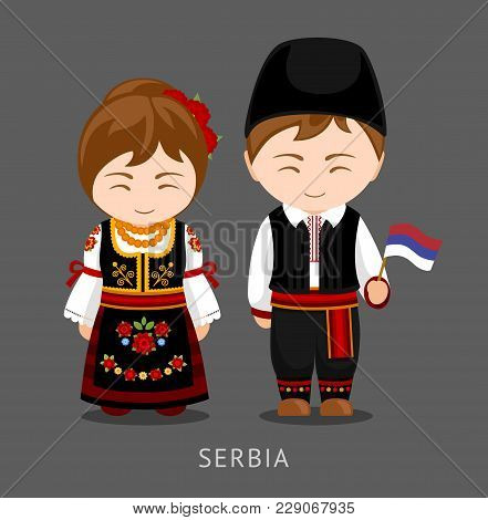 Serbs In National Dress With A Flag. Man And Woman In Traditional Costume. Travel To Serbia. People.