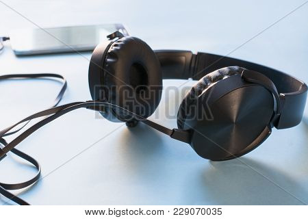 Headphones And Mobile On Blue. Close Up. Audio Technology. Modern Earphone.
