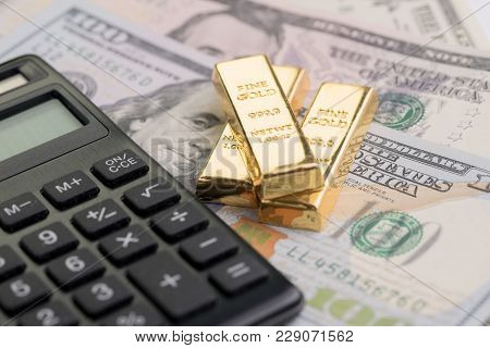 Gold Bars Or Bullion Ingot On Pile Of Money Us Dollar Bills With Calculator, Success Investment Or F