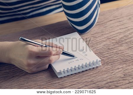 Female Hand Holding Pen Writing Business Plan To Do List On Wood Table In Vintage Color Effect, Task