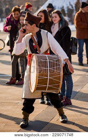 Pernik, Bulgaria - January 26, 2018: Male Drummer In Bulgarian Folklore Costume Speaks On Mobile Pho