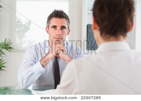 Handsome manager interviewing an applicant in his office