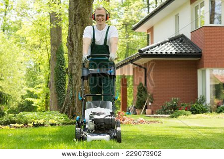 Smiling Young Groundsman Mowing Lawn In Protective Headphones