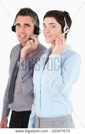 Portrait of operators speaking through headsets against a white background
