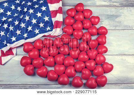 Fifty Red Plastic Hearts And American Flag On A Wooden Surface