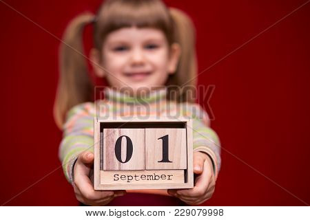 Portrait Of Cheerful Little Girl Isolated On Red Hold Wooden Calendar Set On First September, Focus