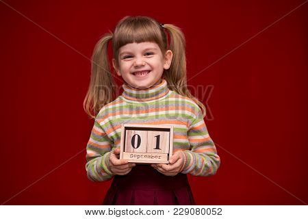 Portrait Of Cheerful Little Girl Isolated On Red Hold Wooden Calendar Set On First September. Back T